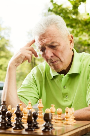Elderly man thinking about next moves in chess. photo