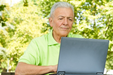 old technology: Senior man using laptop outdoors.
