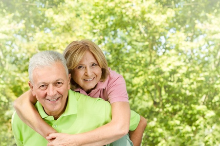 happy old couple: Portrait of happy senior man giving piggyback ride mature woman. Stock Photo