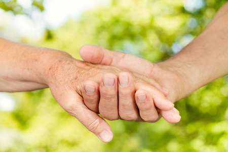 Closeup of old people hands holding together outdoor. photo