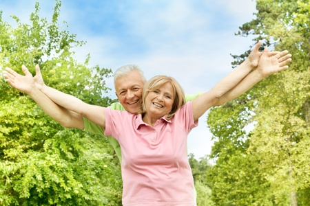 Happy elderly couple with raised arms outdoors. photo