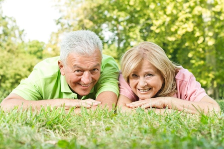Smiling senior couple relaxed on green grass.. photo