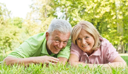 life success: Portrait of happy old people lying on green grass.