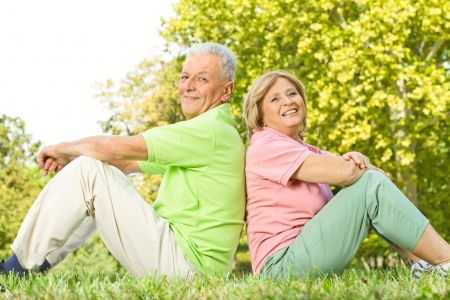 Happy senior couple sitting on grass back to back. Stock Photo - 10760300