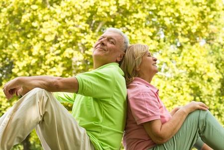 Happy senior Couple entspannt auf grünem Gras Rücken an Rücken. Standard-Bild