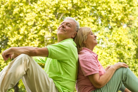 older women: Happy senior couple relaxed on green grass back to back.
