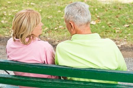 dos personas conversando: Vista posterior de la pareja de ancianos sentados y hablando en el banco del parque.