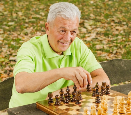 Elderly man playing chess in the park. photo