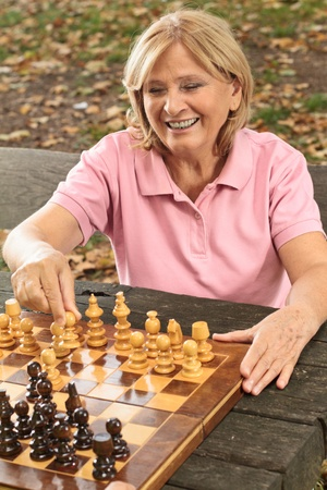 Smiling senior women playing chess on a park bench. photo
