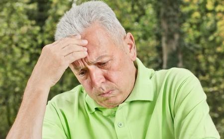 Portrait of worried senior man outdoors.