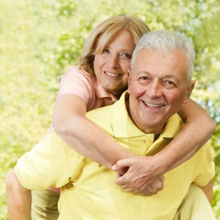 Portrait of happy senior man giving piggyback ride outdoors. photo