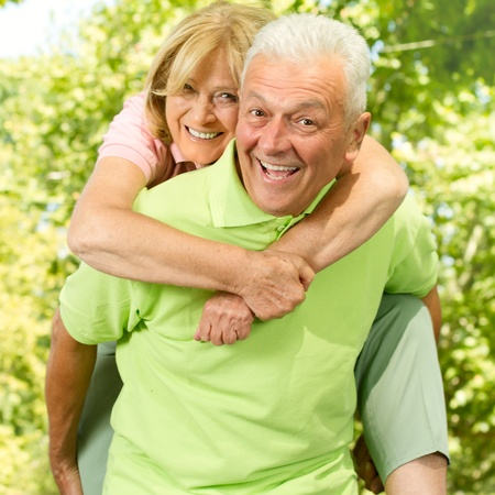 piggyback ride: Portrait of happy senior man giving piggyback ride outdoors. Stock Photo