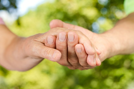 touching hands: Closeup of senior couple hands holding together outdoors.