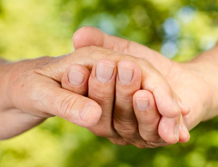 Closeup of senior couple hands holding together outdoors. photo