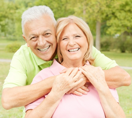 Closeup portrait of happy elderly man embracing mature woman. photo