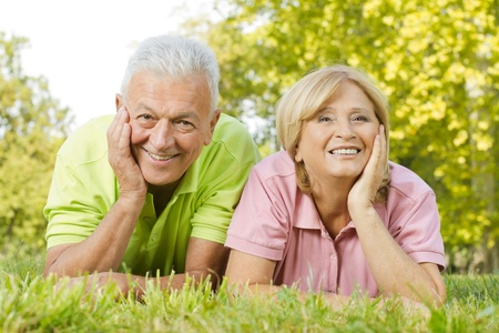 older couples: Portrait of happy old people lying on green grass.