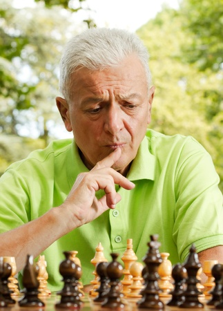 Portrait of worried elderly man playing chess outdoors. Stock Photo