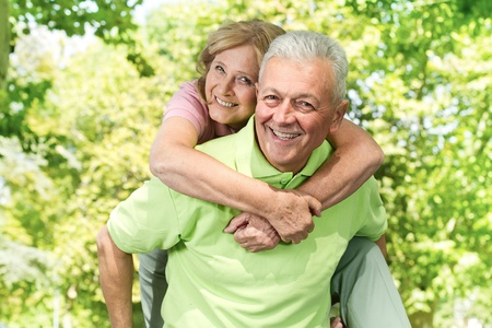 Portrait of happy senior man giving piggyback ride outdoors. Stock Photo