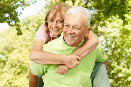 Portrait of happy senior man giving piggyback ride outdoors. Stock Photo - 11212464
