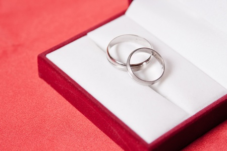 Wedding rings in red box, over red background.