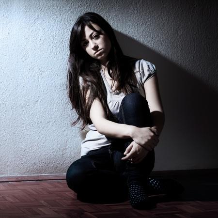 emotional pain: Retrato de ni�a adolescente deprimido sentado en el suelo.