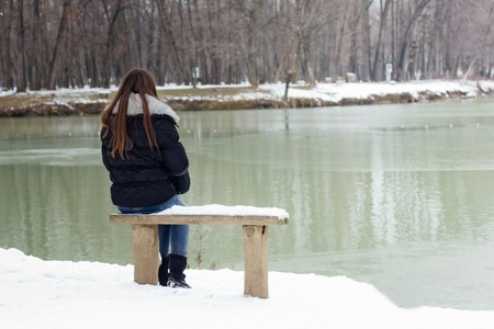 A lonely young woman sitting on a bench beside the lake, winter time. Stockfoto