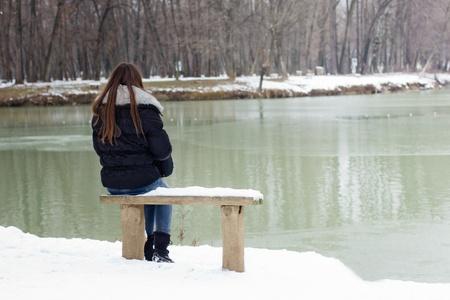 persona deprimida: Una mujer solitaria joven sentado en un banco al lado del lago, el tiempo de invierno.