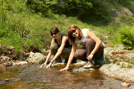 Two girls refreshing with clean water from stream at beautiful spring day. photo