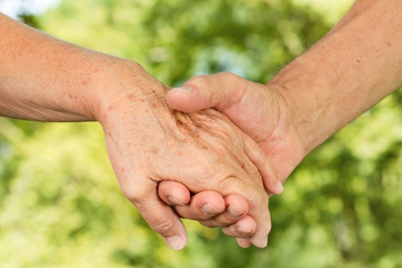 Closeup of old people hands holding together with natural background. photo