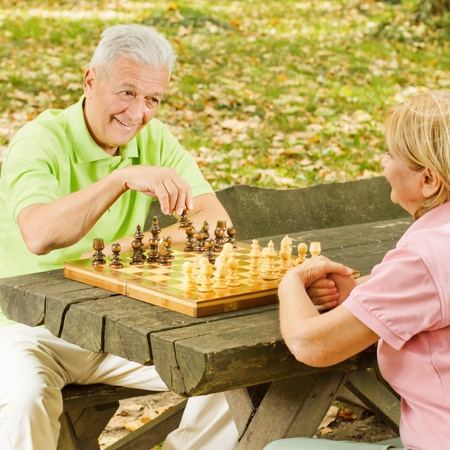 Happy elderly couple has fun playing chess in the park. photo