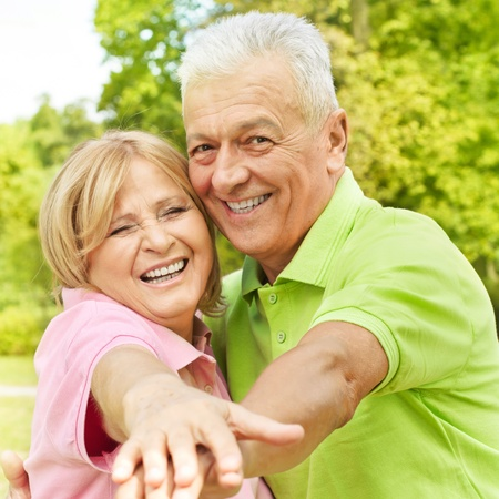 Portrait of happy senior woman and man enjoying in the park. photo