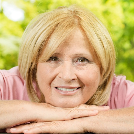 Closeup portrait of smiling senior woman in the park. Stockfoto