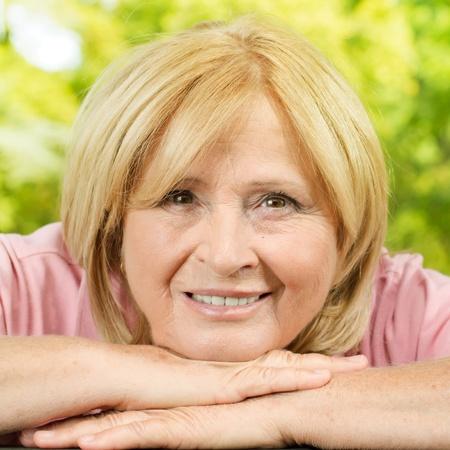 Closeup portrait of smiling senior woman in the park. Standard-Bild
