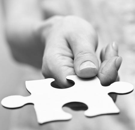 piezas de puzzle: Las manos humanas que sostienen la pieza que falta