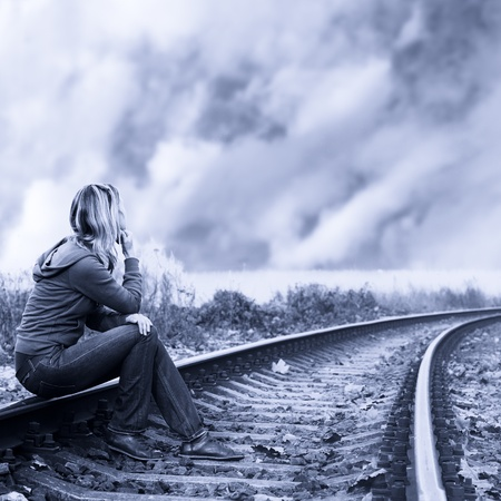 sad lonely girl: Lonely woman sitting on the rails and thinking  Stock Photo