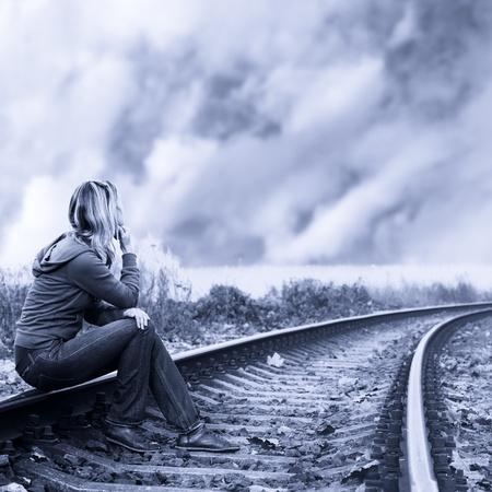 persona triste: Mujer solitaria sentada en los rieles y el pensamiento Foto de archivo