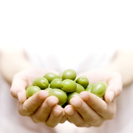 Human hands holding green olive with space for text