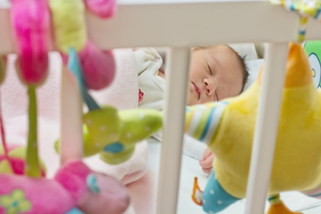 baby crib: Portraot of sleeping newborn baby,view through the fence at the crib