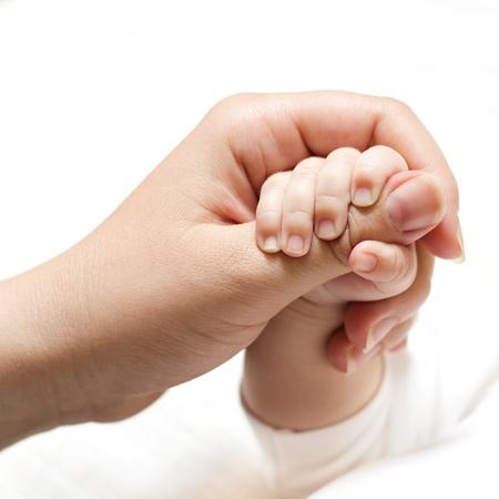 Newborn baby holding mother hand