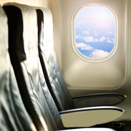 View of the sky and clouds with sunlight from the airplane window,empty seats.