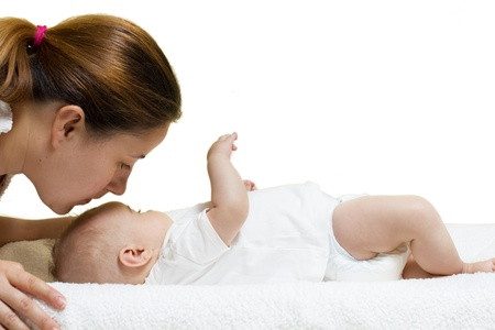 Young mother kissing baby girl while lying on her back on white background. photo