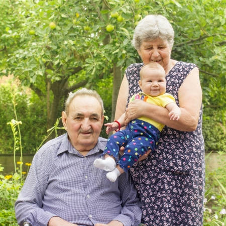 Portrait of an elderly couple with a granddaughter in the backyard Stock Photo - 14959155
