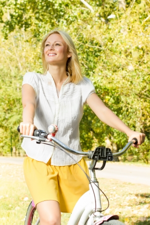 Portrait of an happy smiling young woman riding a bicycle in the park. photo