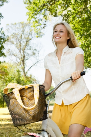 free riding: Portrait of an happy smiling young woman riding a bicycle in the park.Looking at camera. Stock Photo