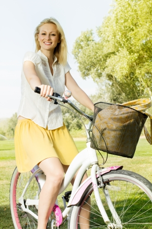 Portrait of an happy smiling young woman riding a bicycle in the park.Looking at camera. Standard-Bild
