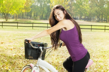 free riding: Portrait of an happy smiling girl riding a bicycle in the park.Looking at camera. Stock Photo