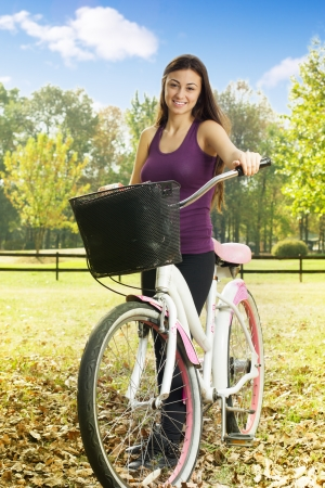 free riding: Cheerful girl with a bicycle enjoying nature in the park