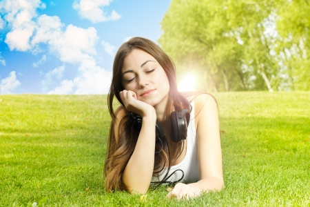 Happiness girl with headphones enjoying nature at sunny day  photo