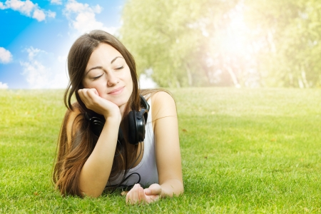 Happiness girl with headphones enjoying nature at sunny day Stock Photo - 15692987