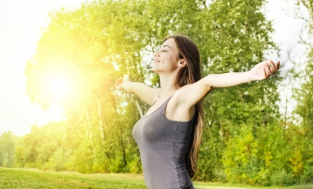 Happiness girl with open hands enjoyment nature at beautiful sunny day  photo